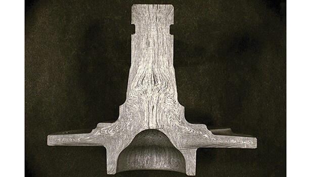 Рисунок 1. Поток зерна можно наблюдать в этой нарезанной части штампованной поковки. Он был разрезан, отполирован и травлен кислотным раствором. Наблюдаемые линии потока обусловлены, прежде всего, частицами и включениями, которые были остатками исходного отливки. Они были деформированы во время процесса конверсии и ковки заготовки. Процесс ковки также выровнял зерна металла в направлении, аналогичном линиям потока на этой картинке.