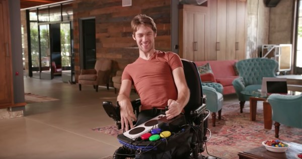Disabled man using Trabasack Curve Connect wheelchair lap tray and bag with games console handset on top