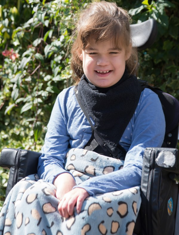 Girl in a wheelchair wearing Seenin kerchief bib in navy