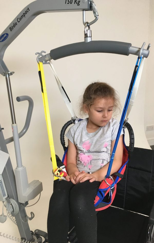 Young disabled girl being moved in ProMove sling with straps attached to the hoist