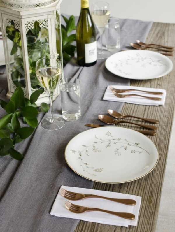Image is a photograph of a wooden table laid with pretty floral decoration, a bottle of wine, plates and Knork cutlery in an Antique Brass finish