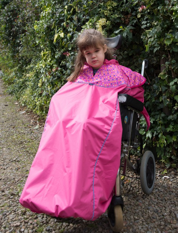 Disabled girl in fuchsia Seenin total waterproof wheelchair cover