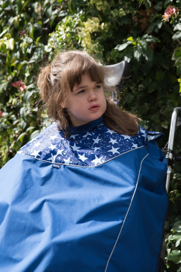 Disabled girl in navy Seenin total waterproof wheelchair cover with white star pattern