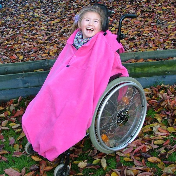 Disabled girl in woodland in fuchsia Seenin total fleece wheelchair cover