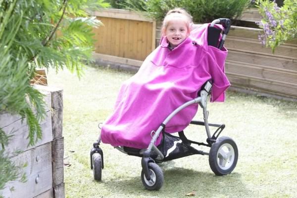 Disabled girl in fuchsia Seenin total fleece wheelchair cover