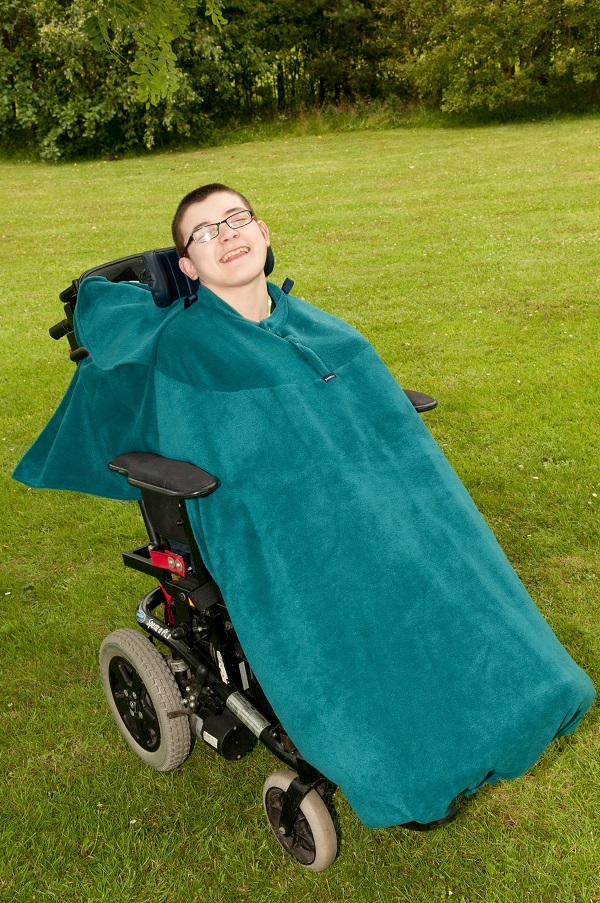 Disabled man in field wearing teal Seenin total fleece wheelchair cover
