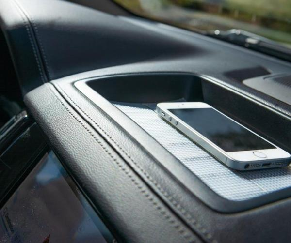 Image is a photograph of a mobile phone sitting atop a strip of Cat Tongue Grip Tape on a car dashboard