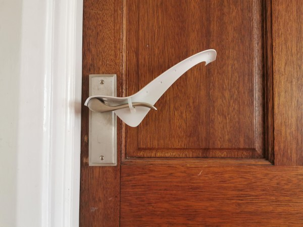 Image is a photograph of a wooden, varnished door with a brushed steel level handle, with a Tru Grip door handle extender attached