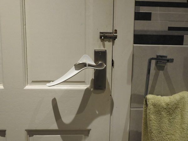 Image is a photograph of a white internal house door with a Try Grip handle extension kit installed upside down to aid those with arthritis