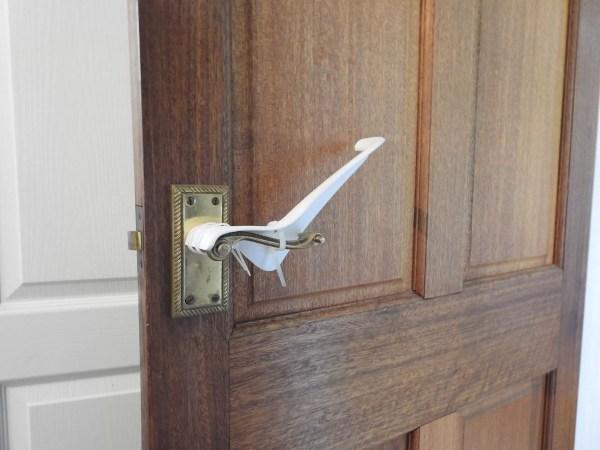 Image is a photograph of a brass internal door handle with a Tru Grip door handle extension kit installed