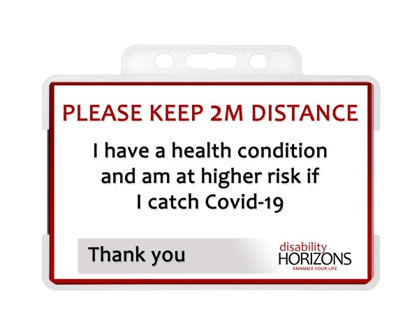 """Image is a plastic ID card to promote social distancing, in a plastic ID card holder. Bright red text in capitals reads: """"PLEASE KEEP 2M DISTANCE"""". Under this black text reads: """"I have a health condition and am at higher risk if I catch Covid-19. Thank you"""". The bottom righthand corner features the Disability Horizons logo."""