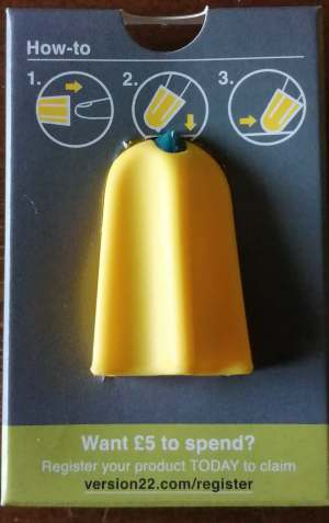 Yellow cone shaped Nimble one finger cutter with ridges in it and a blue sharp tip sat in a blue box with images showing you how to use it by putting it on your finger