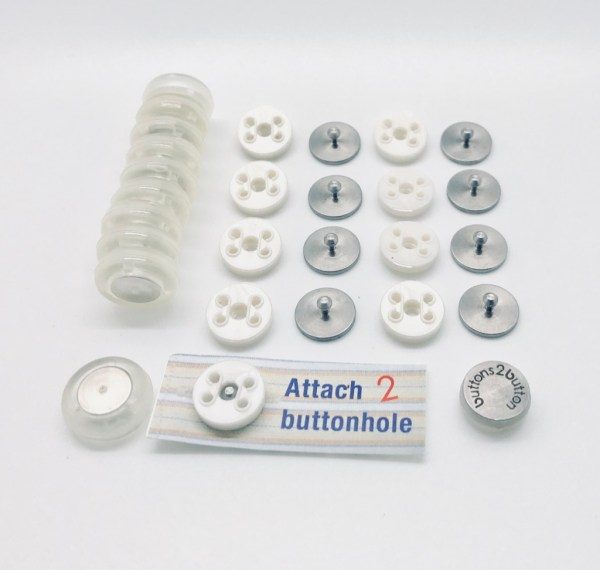 Image is a photograph of the Buttons 2 Button magnetic button kit contents laid-out on a white surface