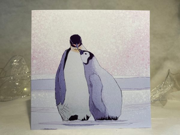 Image is a photograph of an illustrated card featuring a baby penguin looking up to their adult penguin.