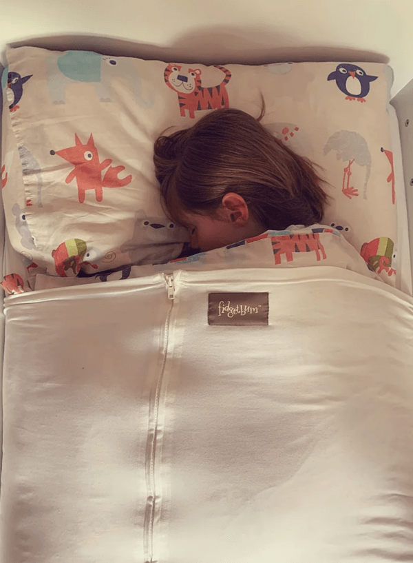 young child fast asleep with the fidgetbum keeping them snug and secure