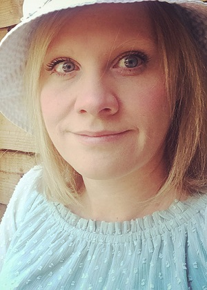 Image is a photograph of Amrick Ainley Disability Horizons shop tech and design manager, wearing a pale green top and white sun hat, smiling whilst sat outdoors.
