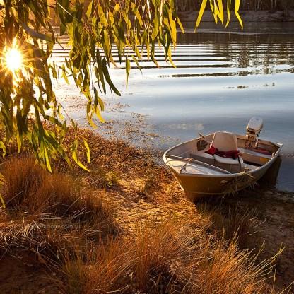 Fishing boat on bank of Murray River setting sun through trees.