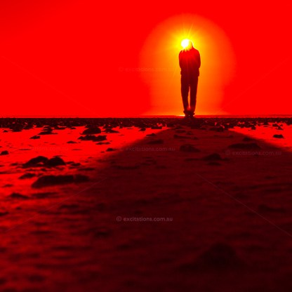 Abstract image of man walking out of a sunrise, red filter applied promotion for Excitations Photo Adventures.