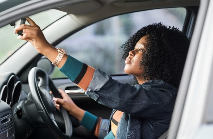 Young woman driver checking rearview mirror before backing out of a parking space