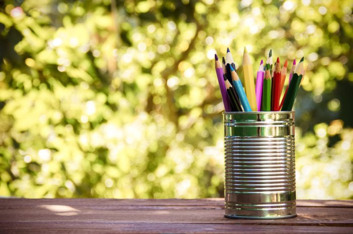 Tin can holding colored pencils on a table outdoors