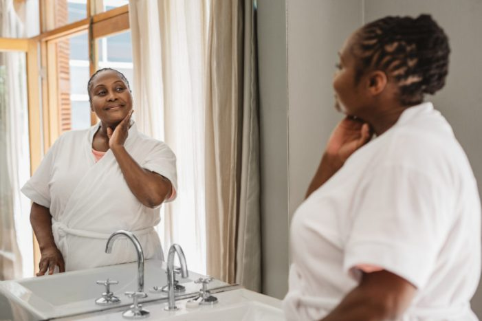 Smiling African American woman wearing a bathrobe looking at her complexion in the mirror while standing in her bathroom in the morning