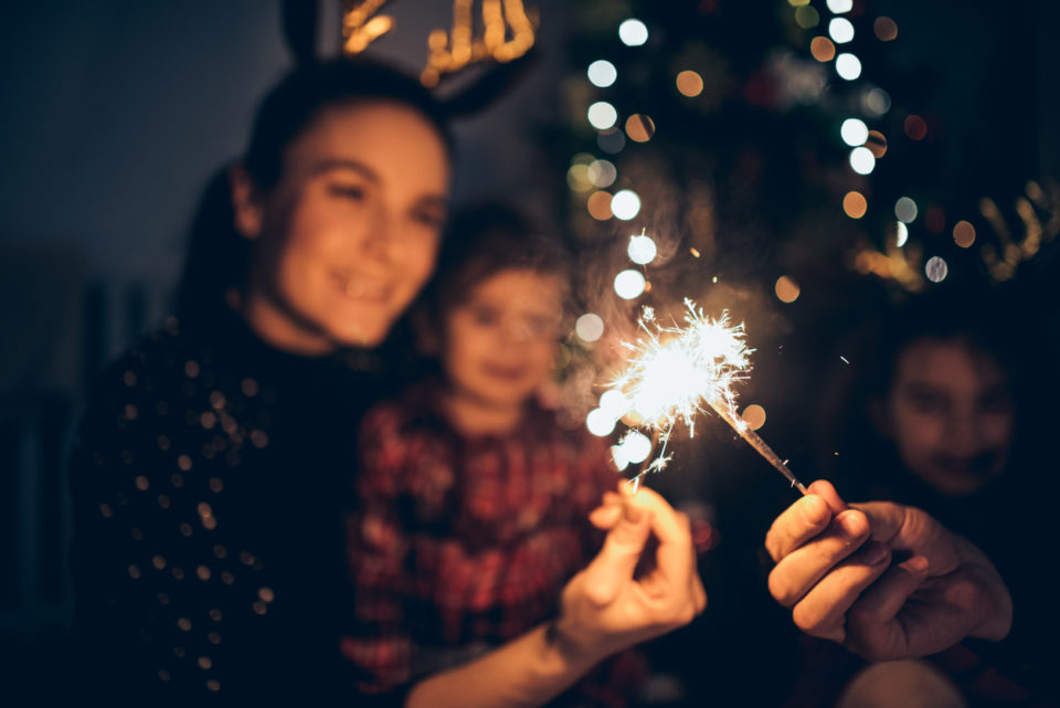 A family New Year's Eve party with hats and sparklers