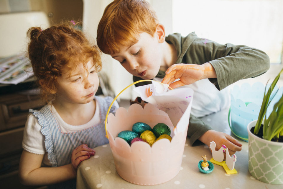 Young siblings stealing chocolate easter eggs out of a pink bucket after an easter egg hunt.
