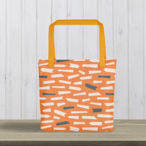 orange arrows tote bag with yellow handles on table