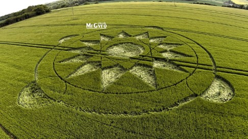 Manton Drove, Nr. Marlborough, Wiltshire. 24 May 2015. Wheat. c. 90ft diameter, A central flattened circle surrounded by a tracery of fine lines depicting triangles with an outer set of 13 lozenge shapes. The tips touching a circular line; all within an outer circle with four outer circles bisected by the outer circular line.