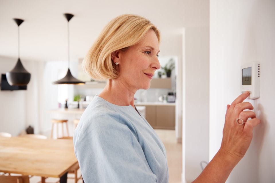 Close Up Of Woman Adjusting Central Heating Temperature At Home On Thermostat
