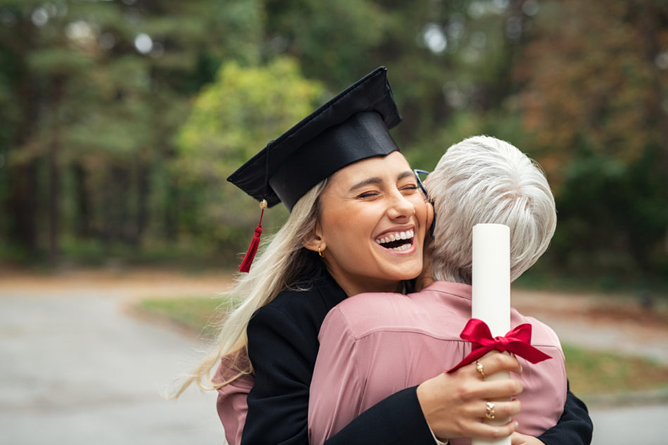 Excited graduate hugging mother