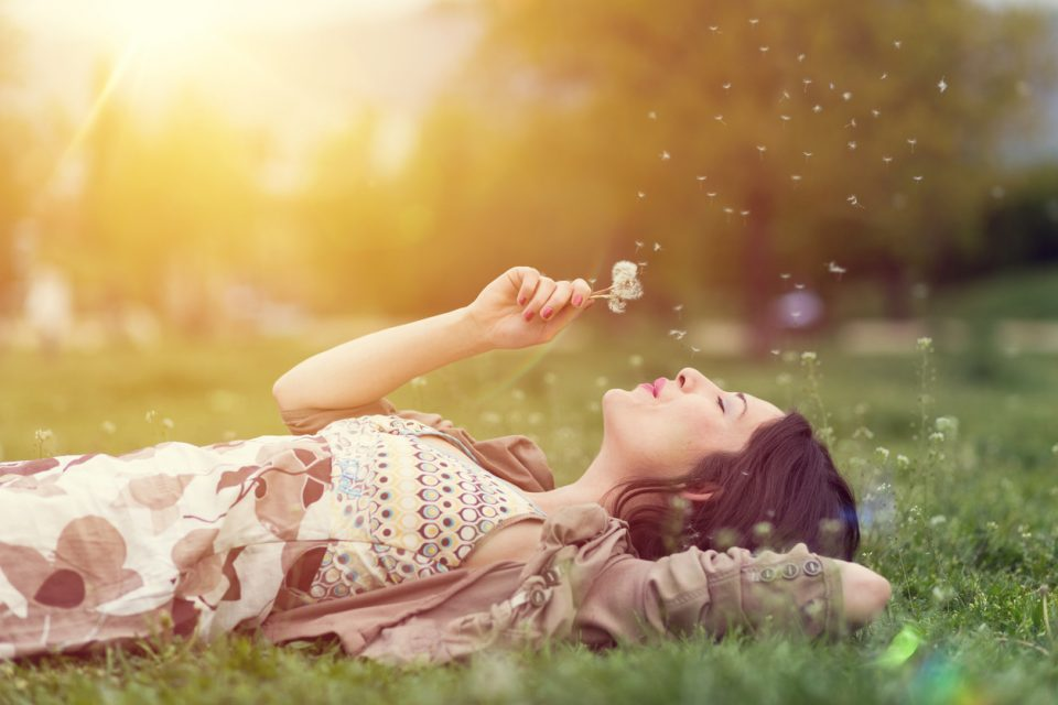 woman in the park blowing dandelion in spring