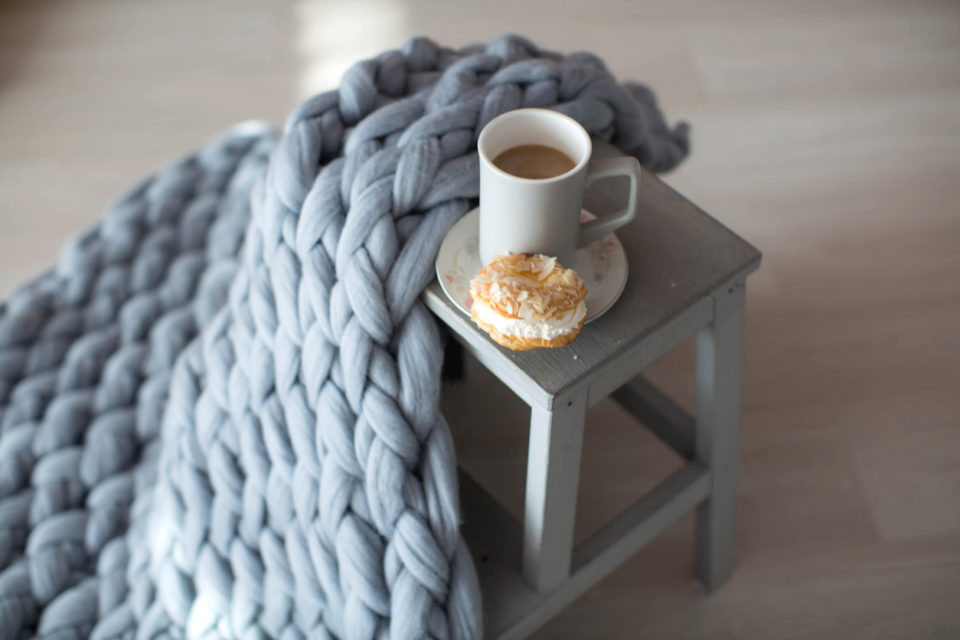 A Blue-Gray chunky-knit blanket draped over a gray stool with a cookie and a cup of coffee.