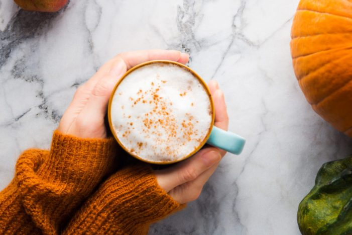 Two hands holding a pumpkin coffee drink