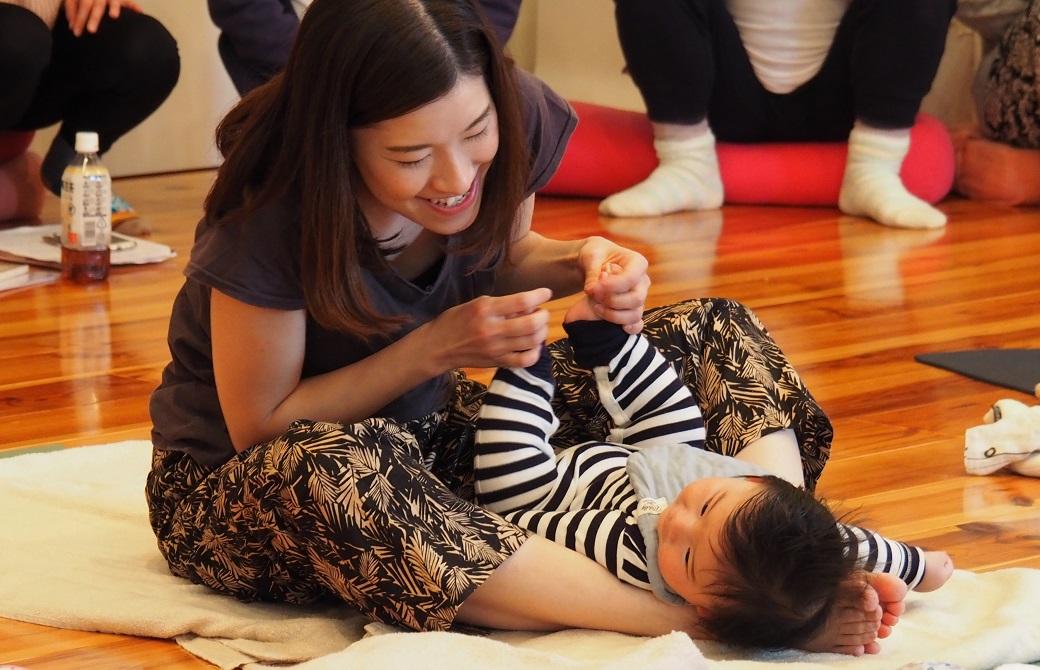 赤ちゃんを寝かせて笑顔で見つめるお母さん:産後ヨガクラス風景