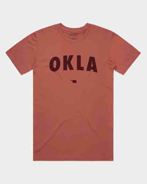 A mockup of a coral tee shirt with OKLA screenprinted in burgundy across the front