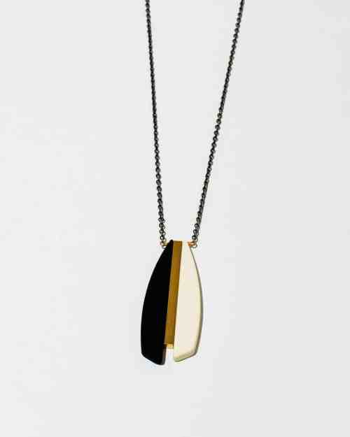 A cream colored stone necklace on a gold chain