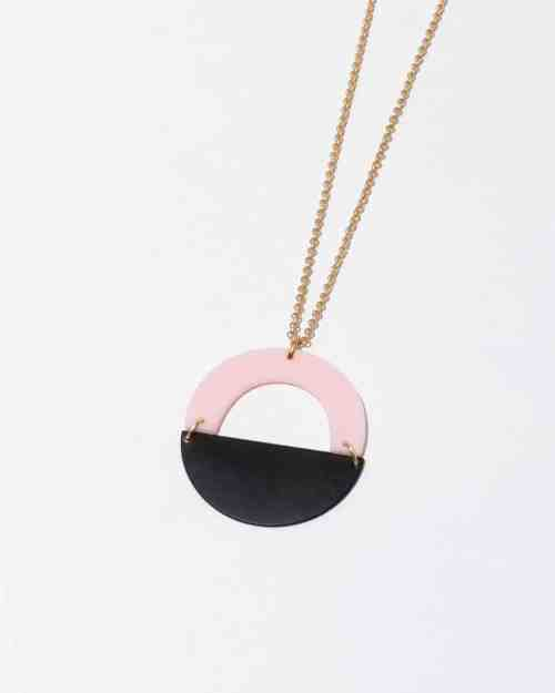 A brass necklace with pink and onyx stones on the end