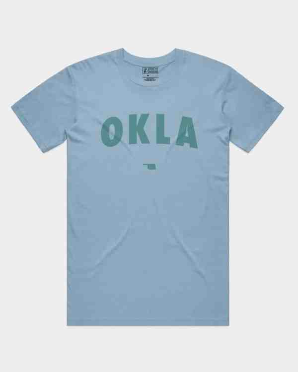 A mockup of a blue shirt with OKLA across the front in turquoise ink