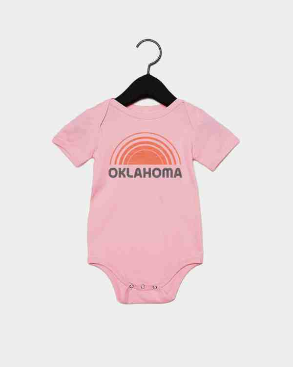A mockup of a pink kid's onesie that says Oklahoma with a sun above it.