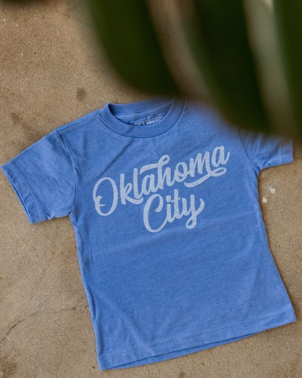 A photo of a blue kids tee that says Oklahoma City in white ink