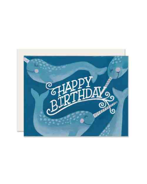 A blue card with narwhales on the front that says 'Happy Birthday.'