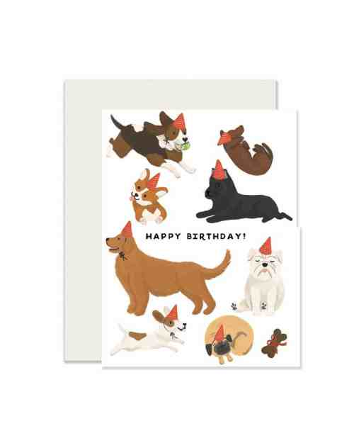 A white card with brown dogs in party hats on it that says, 'Happy Birthday.'
