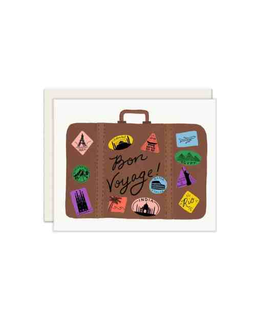 A white paper card with a brown suitcase on it that says Bon Voyage surrounded by stickers