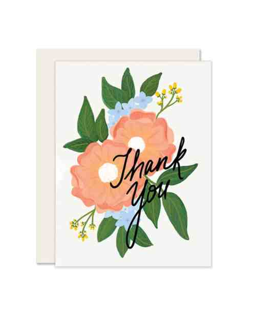 A white paper card that says Thank You surrounded by flowers