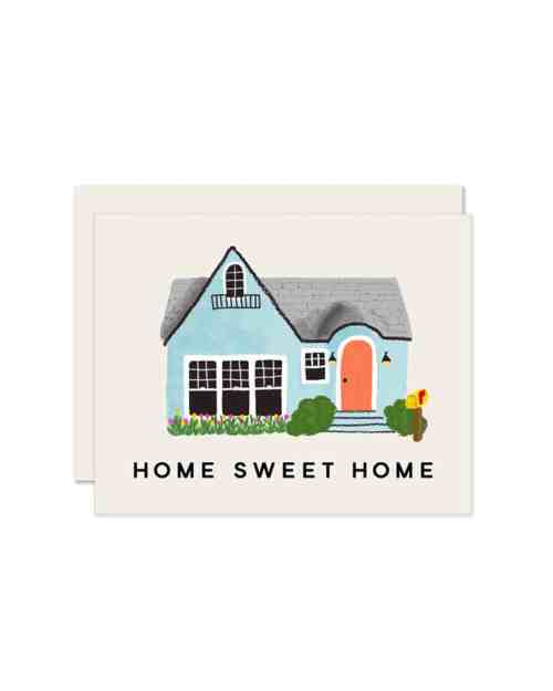 A white paper card that says Home Sweet Home on the front with a house printed on it.