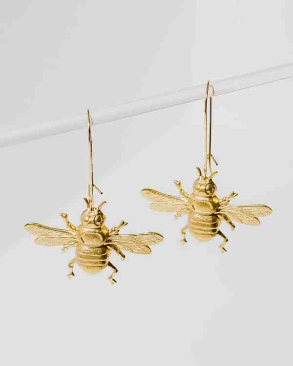 Brass earrings shaped like bumble bees