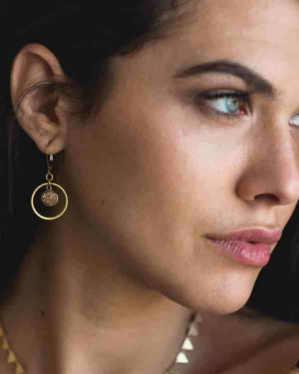 A model wearing a pair of gold kamilah earrings
