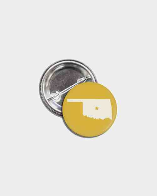 A gold tin pinback button with the state of Oklahoma on it in white.
