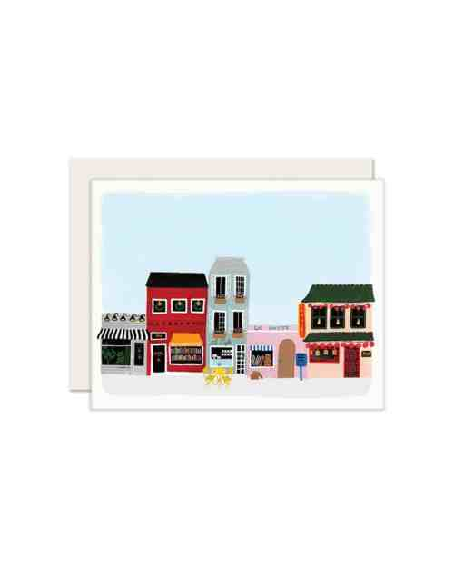 A card with a downtown scene printed on it with a blue sky overhead
